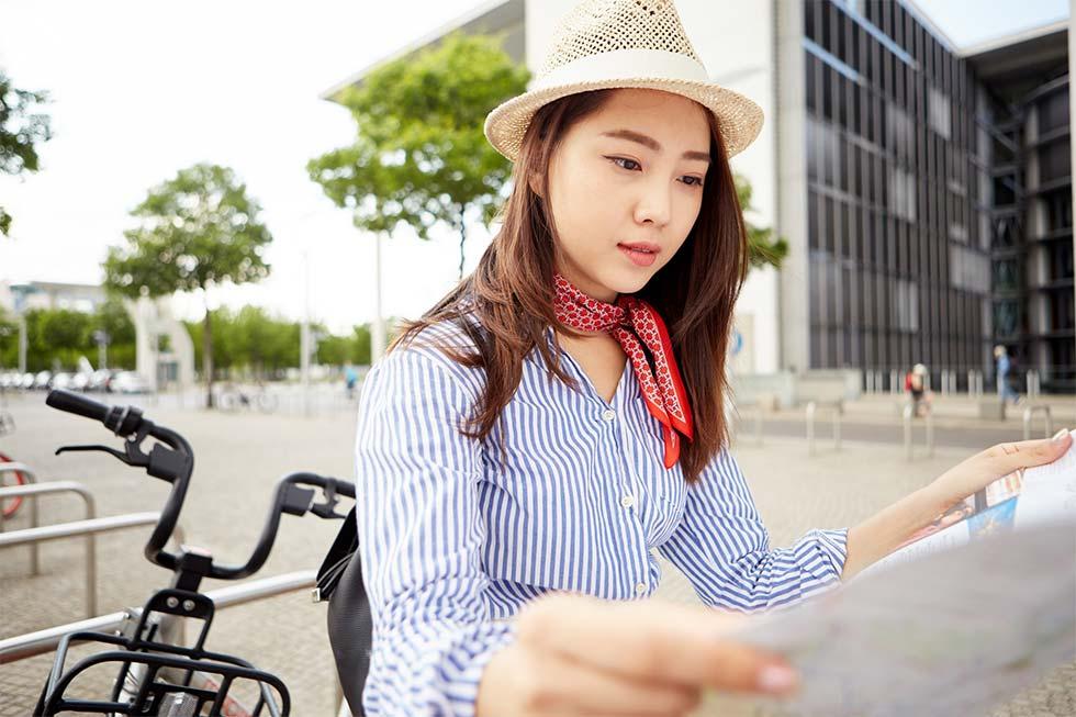 自転車から降りて地図を見る女性